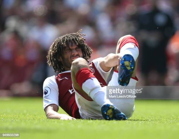 Mohamed Elneny of Arsenal holds his injured left leg during the Premier League match between Arsenal and West Ham United at Emirates Stadium on April...