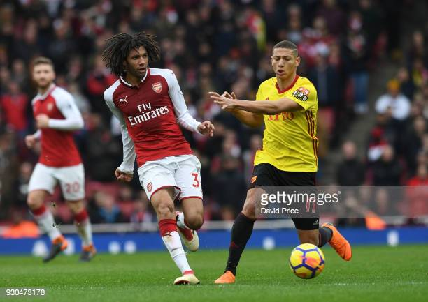 Mohamed Elneny of Arsenal passes the ball under pressure from Richarlison of Watford during the Premier League match between Arsenal and Watford at...