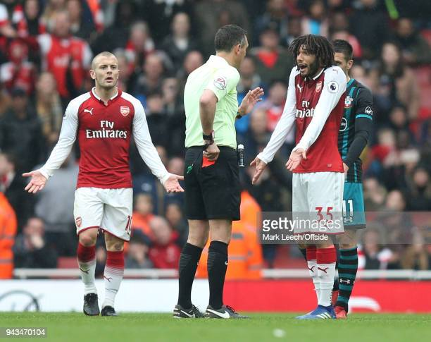 Mohamed Elneny of Arsenal reacts as referee Andre Marriner puts his red card back in his pocket during the Premier League match between Arsenal and...