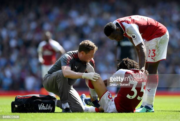 Mohamed Elneny of Arsenal receives treatment from the medical team during the Premier League match between Arsenal and West Ham United at Emirates...