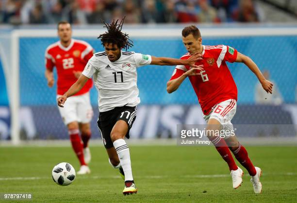 Mohamed Elneny of Egypt battles for possession with Denis Cheryshev of Russia during the 2018 FIFA World Cup Russia group A match between Russia and...
