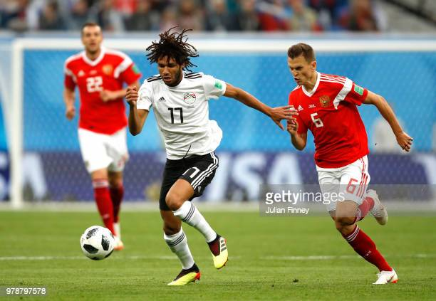 Mohamed Elneny of Egypt runs with the ball under pressure from Denis Cheryshev of Russia during the 2018 FIFA World Cup Russia group A match between...