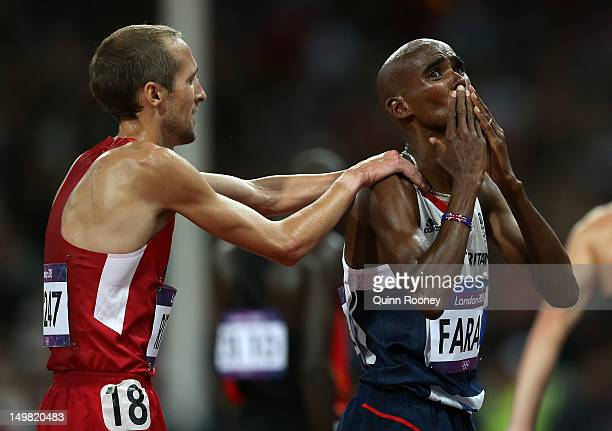 Mohamed Farah of Great Britain celebrates winning the gold medal in Men's 10000m Final with Dathan Ritzenhein of the United States on Day 8 of the...