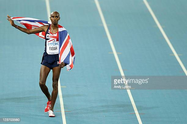 Mohamed Farah of Great Britain celebrates with his country's flag after claiming victory in the men's 5000 metres final during day nine of 13th IAAF...