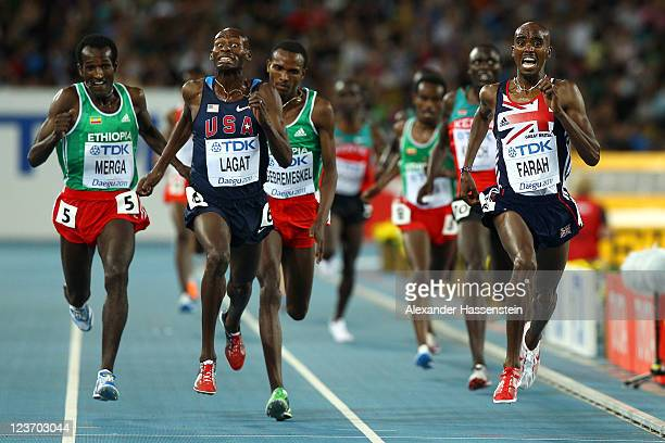 Mohamed Farah of Great Britain crosses the finish line ahead of Bernard Lagat of the USA to claim victory in the men's 5000 metres final during day...