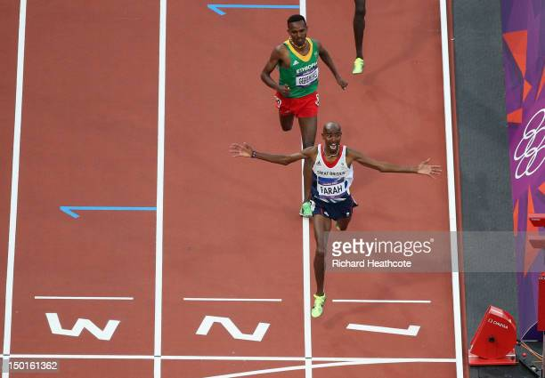 Mohamed Farah of Great Britain crosses the finish line to win gold ahead of Dejen Gebremeskel of Ethiopia in the Men's 5000m Final on Day 15 of the...
