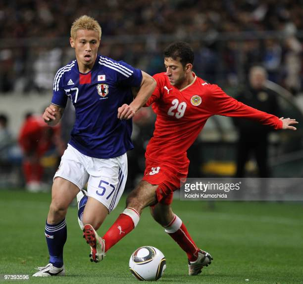 Mohamed Hubail of Bahrain competes with Keisuke Honda of Japan during the AFC Asian Cup Qatar 2011 Group A qualifier football match between Japan and...