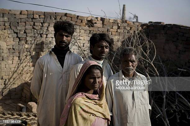 Mohamed Ijaz poses for a portrait with his wife Farzana Ijaz brother Mohamed Riiz and father Karm Ali outside their house at a brick factory in...