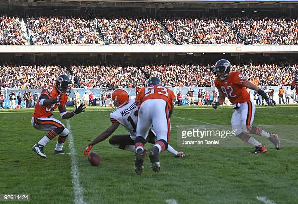 Mohamed Massaquoi of the Cleveland Browns fumbles as Charles Tillman Nick Roach and Hunter Hillenmeyer of the Chicago Bears move to the ball at...