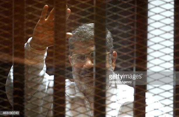 Mohamed Morsi stands inside a glass defendant's cage during first session in the trial where Morsi and 10 other codefendants face on charges of...