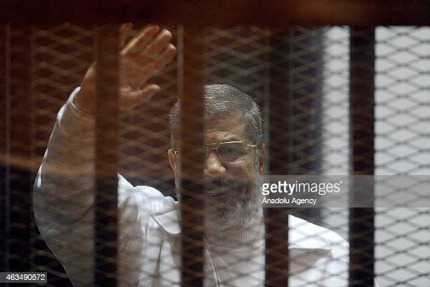 Mohamed Morsi stands inside a glass defendant's cage during first session in the trial where Morsi and 10 other co-defendants face on charges of...