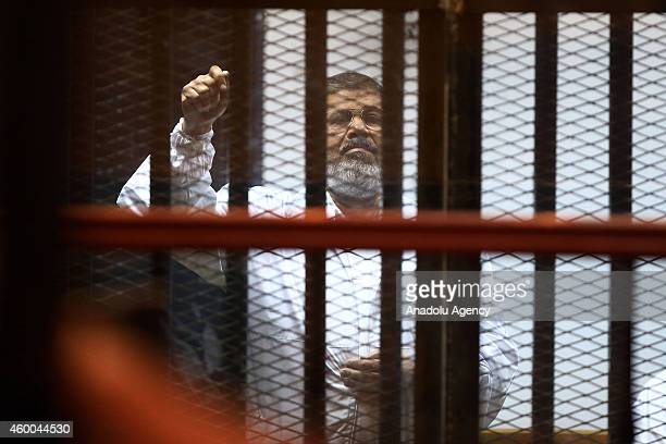 Mohamed Morsi stands inside a glass defendant's cage during his trial at Police Academy in the east of Cairo Egypt on December 6 2014 Morsi and his...