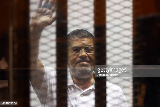 Mohamed Morsi waves as he stands inside a glass defendant's cage during his trial in Cairo, Egypt, on July 07, 2014. An Egyptian court on Monday...