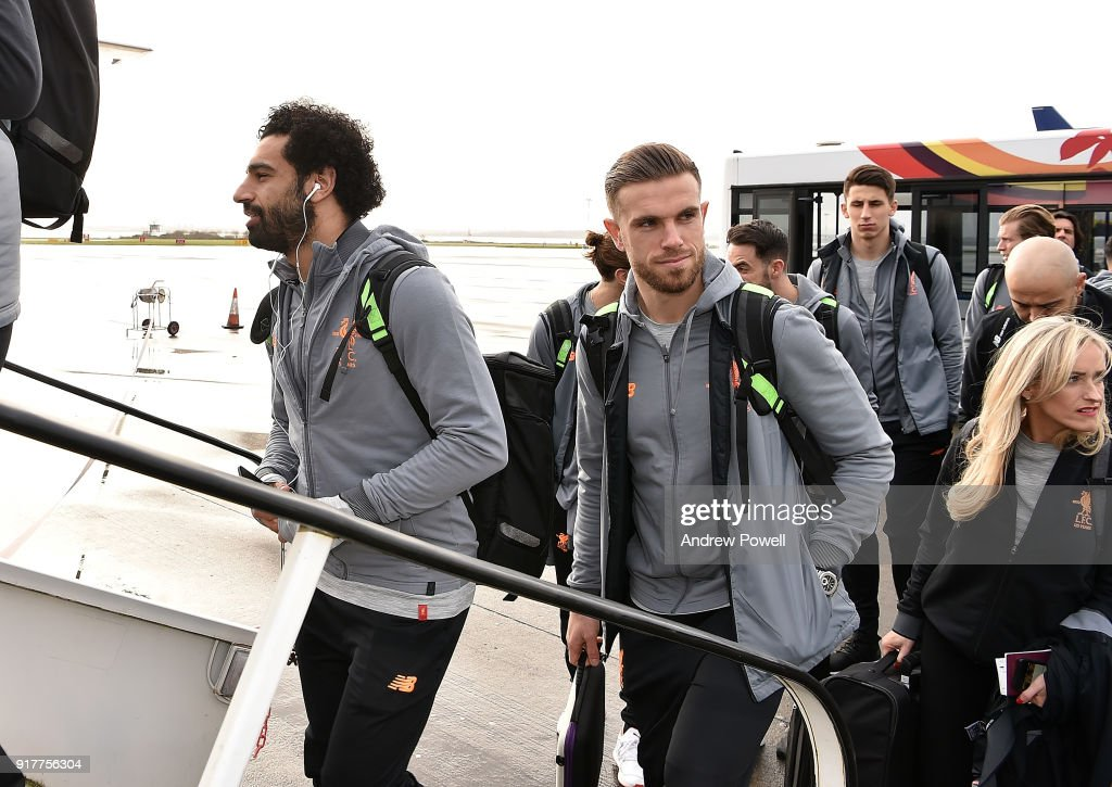 Mohamed Salah and Jordan Henderson of Liverpool board the plane for their trip to Porto at Liverpool John Lennon Airport on February 13, 2018 in Liverpool, England.