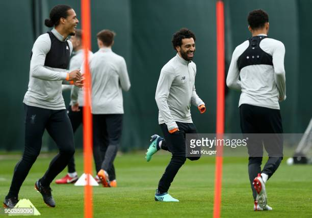Mohamed Salah and Virgil van Dijk of Liverpool warm up during a training session on April 23 2018 in Liverpool England