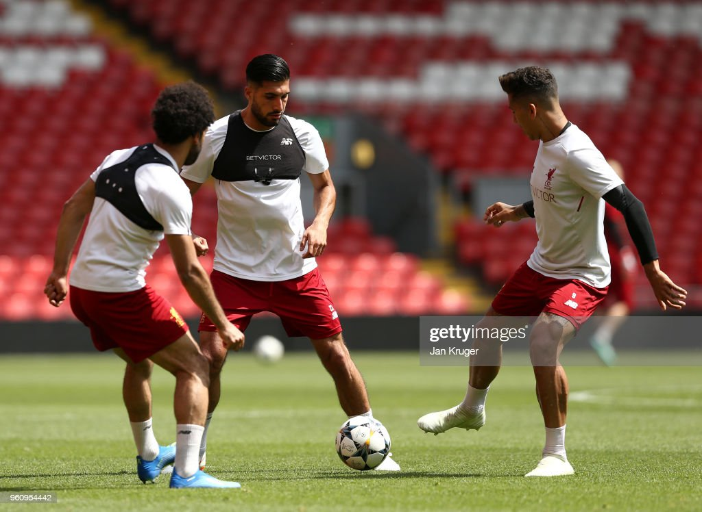 Mohamed Salah, Emre Can and Roberto Firmino of Liverpool pass the ball during a training session at Anfield on May 21, 2018 in Liverpool, England.