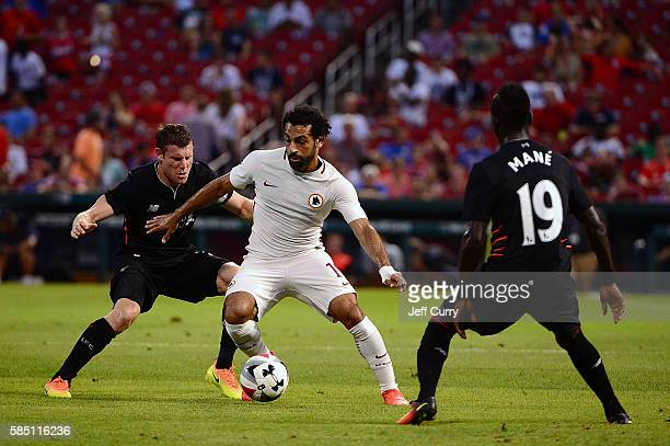 Mohamed Salah of AS Roma handles the ball as James Milner and Sadio Man of Liverpool FC defends during a friendly match at Busch Stadium on August 1...