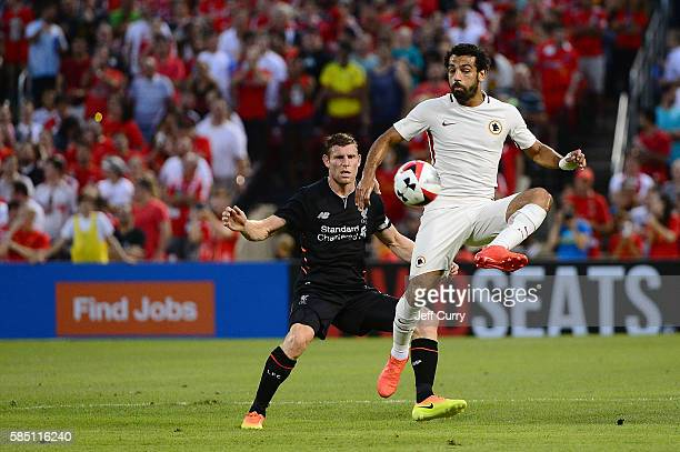 Mohamed Salah of AS Roma handles the ball as James Milner of Liverpool FC defends during a friendly match at Busch Stadium on August 1 2016 in St...