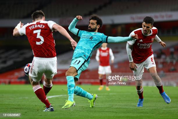 Mohamed Salah of Liverpool battles for possession with Kieran Tierney and Dani Ceballos of Arsenal during the Premier League match between Arsenal...