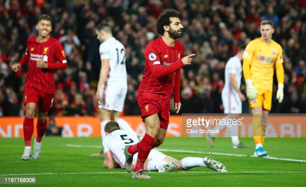 Mohamed Salah of Liverpool celebrates after scoring his team's first goal as Dean Henderson of Sheffield United reacts during the Premier League...