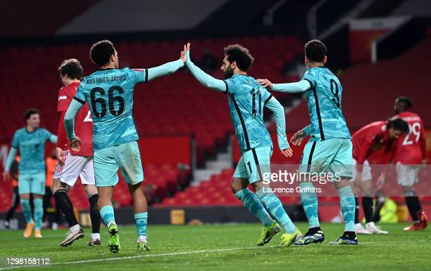 Mohamed Salah of Liverpool celebrates after scoring their sides second goal with team mates Trent Alexander-Arnold and Roberto Firmino during The...
