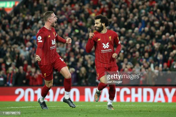 Mohamed Salah of Liverpool celebrates as he scores his team's second goal from a penalty with Jordan Henderson during the Premier League match...