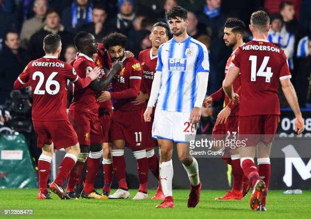 Mohamed Salah of Liverpool celebrates as he scores their third goal from the penalty spot with team mates during the Premier League match between...