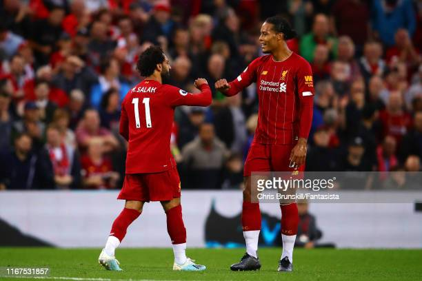 Mohamed Salah of Liverpool celebrates scoring his side's second goal with teammate Virgil van Dijk during the Premier League match between Liverpool...