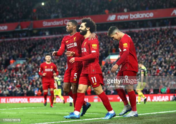 Mohamed Salah of Liverpool celebrates with Georginio Wijnaldum and Roberto Firmino after scoring his team's third goal during the Premier League...