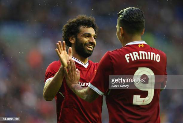 Mohamed Salah of Liverpool celebrates with Roberto Firmino after scoring their first goal during the preseason friendly match between Wigan Athletic...