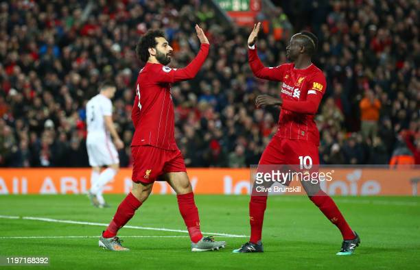 Mohamed Salah of Liverpool celebrates with Sadio Mane after scoring his team's first goal during the Premier League match between Liverpool FC and...