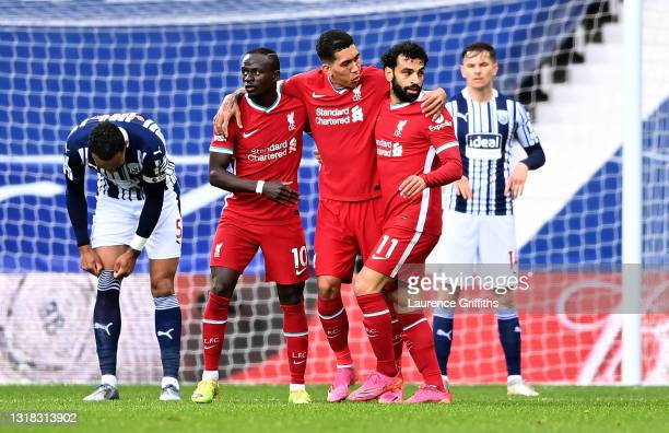 Mohamed Salah of Liverpool celebrates with Sadio Mane and Roberto Firmino after scoring their team's first goal as Kyle Bartley of West Bromwich...
