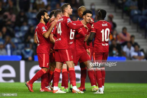 Mohamed Salah of Liverpool celebrates with team mates Jordan Henderson and Sadio Mane after scoring their sides third goal during the UEFA Champions...