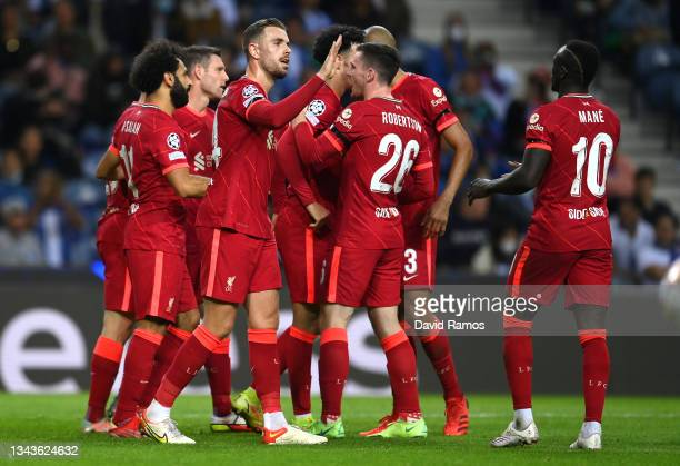 Mohamed Salah of Liverpool celebrates with team mates Jordan Henderson, Andrew Robertson and Sadio Mane after scoring their sides third goal during...
