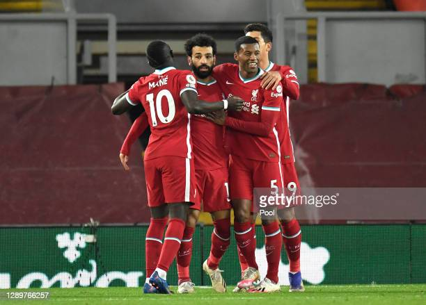 Mohamed Salah of Liverpool celebrates with team mates Sadio Mane, Georginio Wijnaldum and Roberto Firminho of Liverpool after scoring their sides...