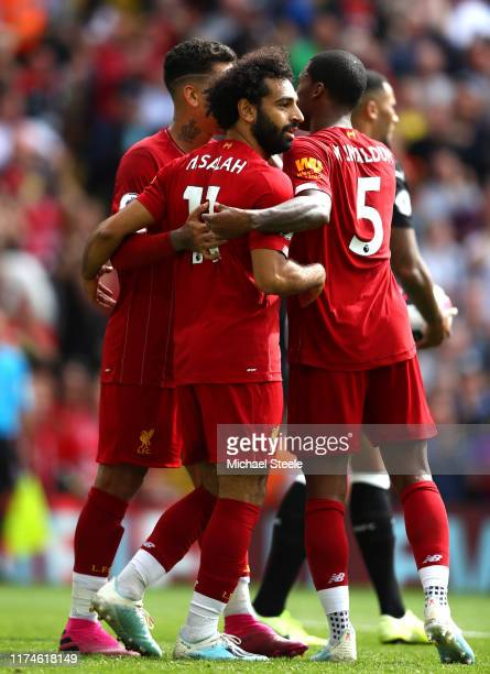Mohamed Salah of Liverpool celebrates with teammates after scoring his team's third goal during the Premier League match between Liverpool FC and...