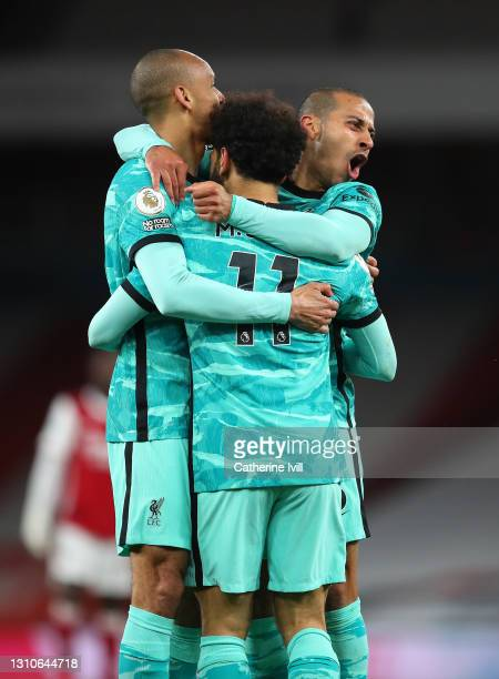 Mohamed Salah of Liverpool celebrates with teammates Fabinho and Thiago Alcantara after scoring their team's second goal during the Premier League...