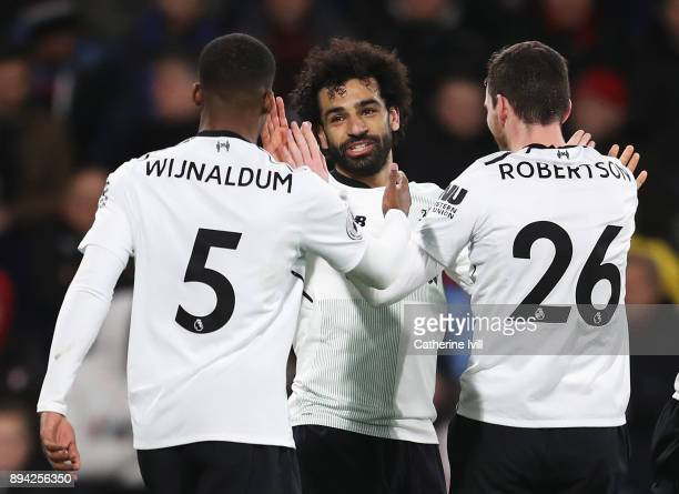 Mohamed Salah of Liverpool celebrates with teammates Georginio Wijnaldum and Andy Robertson after scoring his sides third goal during the Premier...