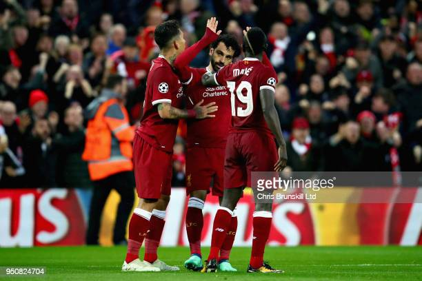 Mohamed Salah of Liverpool celebrates with teammates Roberto Firmino and Sadio Mane after scoring his sides first goal during the UEFA Champions...