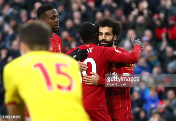 Mohamed Salah of Liverpool celebrates with teammates Sadio Mane and Divock Origi after scoring their team's second goal during the Premier League...