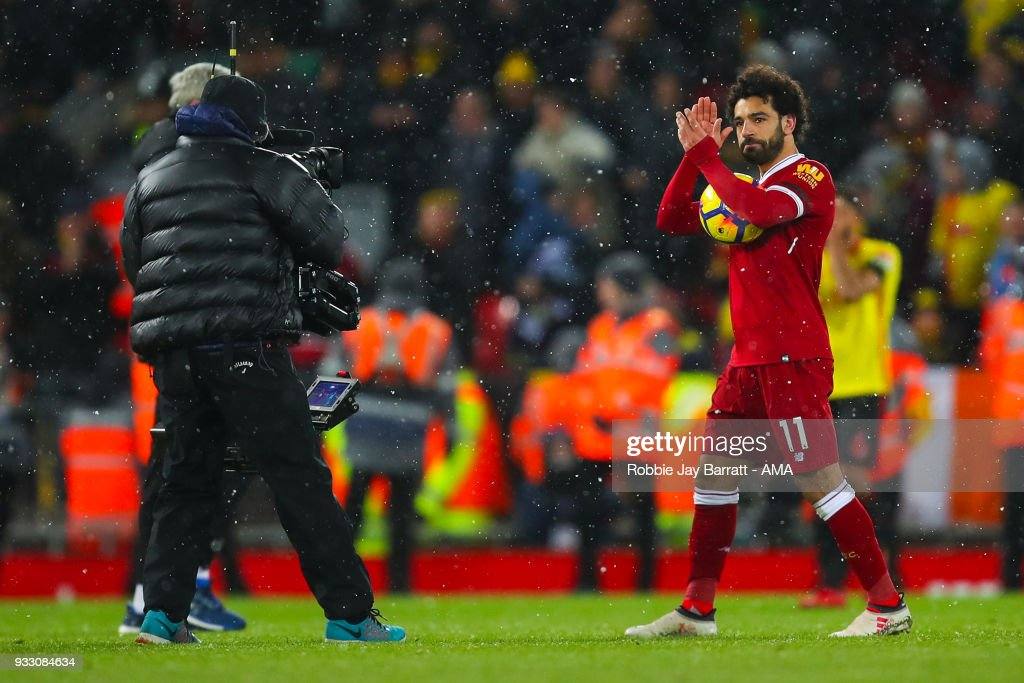 Mohamed Salah of Liverpool celebrates with the match ball at full time during the Premier League match between Liverpool and Watford at Anfield on March 17, 2018 in Liverpool, England.