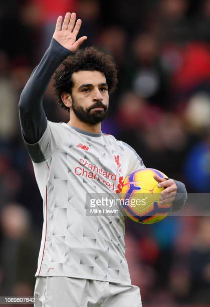 Mohamed Salah of Liverpool collects the match ball after scoring a hattrick and acknowledges the fans after the Premier League match between AFC...