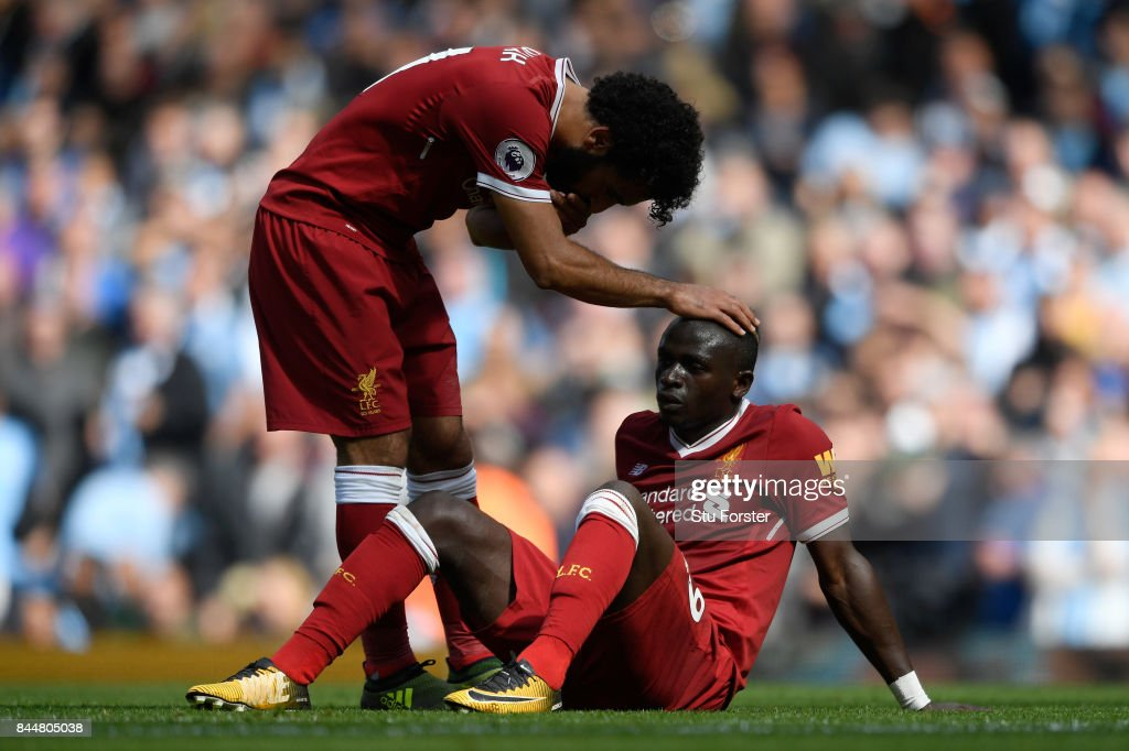 Mohamed Salah of Liverpool comforts Sadio Mane of Liverpool after he reacts to being sent off during the Premier League match between Manchester City and Liverpool at Etihad Stadium on September 9, 2017 in Manchester, England.