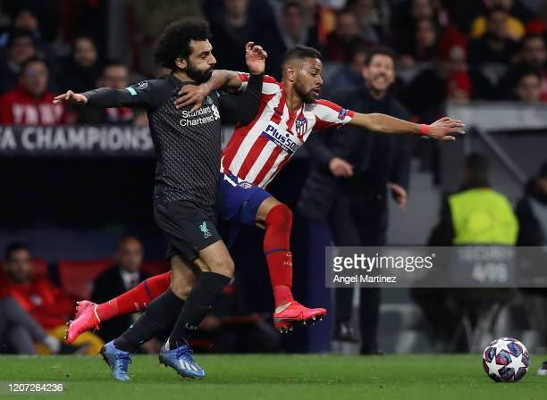Mohamed Salah of Liverpool competes for the ball with Renan Lodi of Atletico de Madrid during the UEFA Champions League round of 16 first leg match...