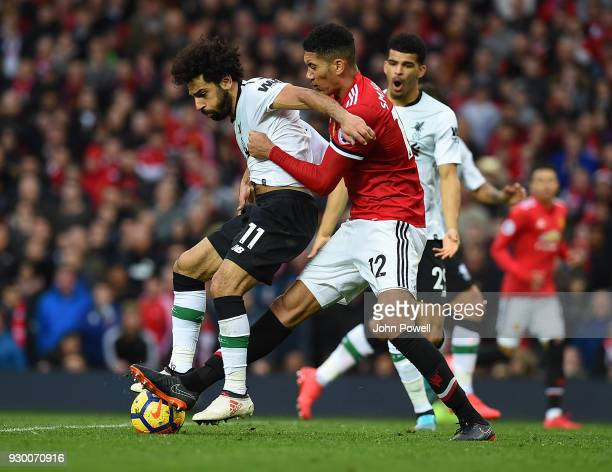 Mohamed Salah of Liverpool competes with Chris Smalling of Manchester United during the Premier League match between Manchester United and Liverpool...