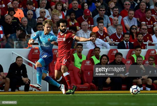 Mohamed Salah of Liverpool competes with Nacho Monreal of Arsenal during the Premier League match between Liverpool and Arsenal at Anfield on August...