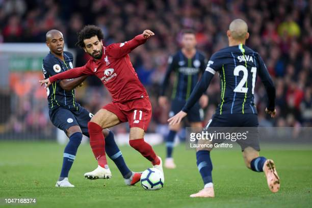 Mohamed Salah of Liverpool controls the ball under pressure from Fernandinho and David Silva of Manchester City during the Premier League match...