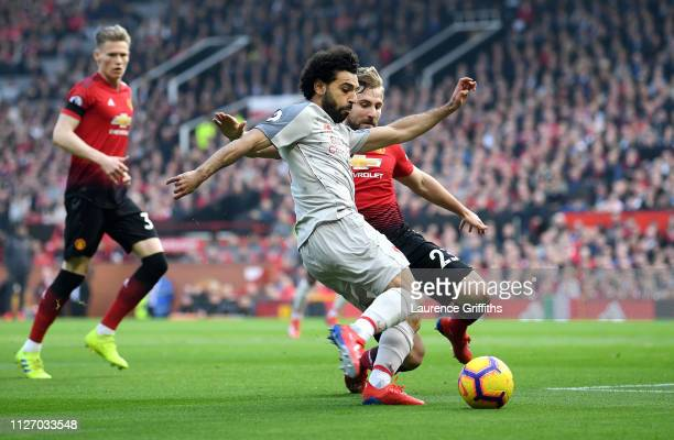 Mohamed Salah of Liverpool crosses the ball under pressure from Luke Shaw of Manchester United during the Premier League match between Manchester...