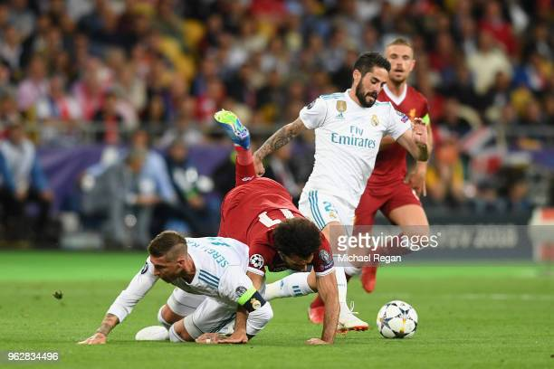 Mohamed Salah of Liverpool falls and lands on his shoulder after a collision with Sergio Ramos of Real Madrid leading to him going off injured during...