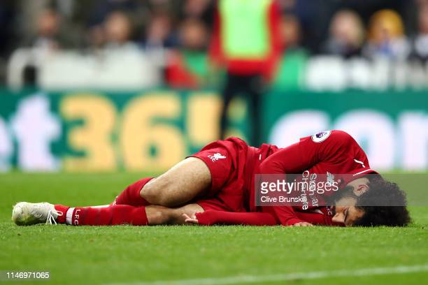 Mohamed Salah of Liverpool goes down injured during the Premier League match between Newcastle United and Liverpool FC at St James Park on May 04...